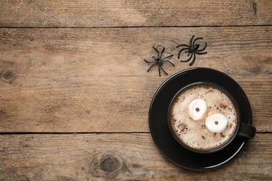 Cup of coffee decorated with marshmallow eyes and space for text on wooden table, flat lay. Halloween celebration