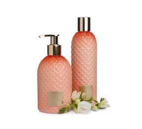 Stylish bottles with cosmetic products and flowers on white background