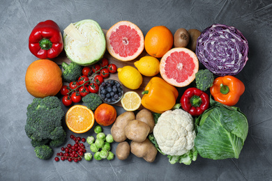 Different products rich in vitamin C on grey table, flat lay