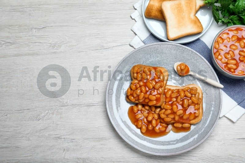 Toasts with delicious canned beans on white wooden table, flat lay. Space for text