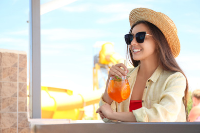 Woman with glass of refreshing drink outdoors. Space for text