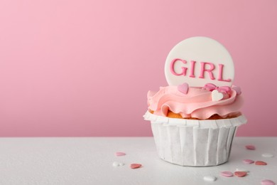 Baby shower cupcake with Girl topper on white table against pink background, space for text