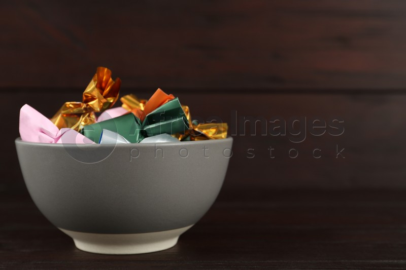 Candies in colorful wrappers on wooden table. Space for text