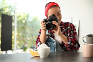 Young photographer taking picture of cups at table indoors