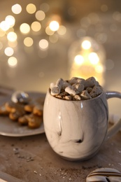 Cup of tasty hot drink and cookies on wooden table, space for text. Christmas atmosphere