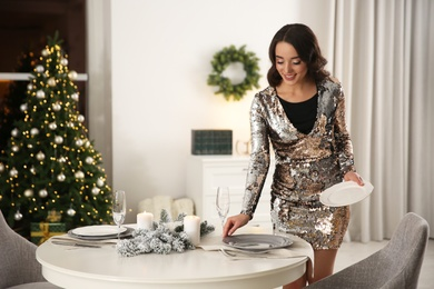 Young woman setting table for Christmas dinner at home