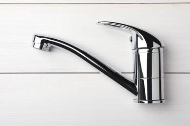Single handle water tap on white wooden table, top view
