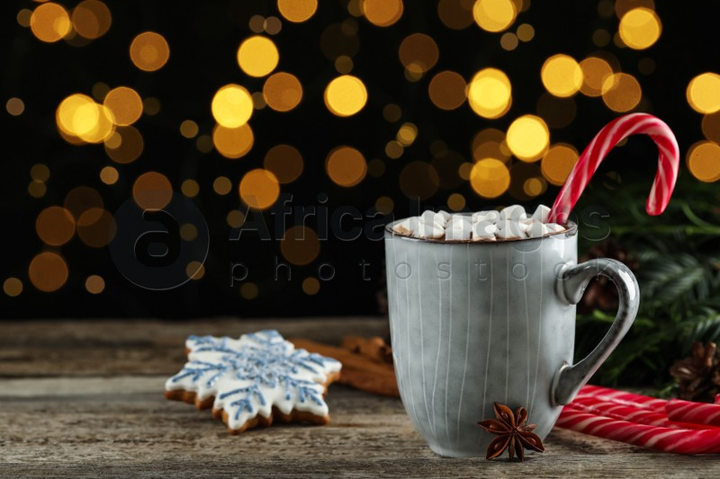 Delicious hot chocolate with marshmallows and candy cane on wooden table against blurred lights, space for text