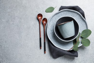 Set of dishware with eucalyptus leaves and napkin on grey table, flat lay. Space for text