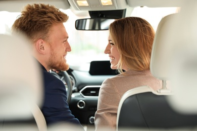 Happy young man and woman in modern car, back view