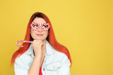 Young woman with bright dyed hair holding candy canes on yellow background. Space for text