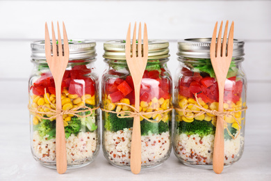 Glass jars with healthy meal on white wooden table