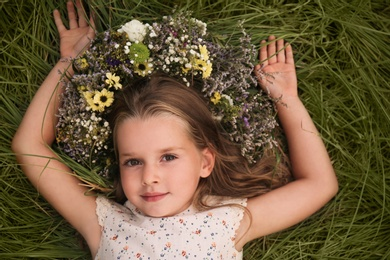Cute little girl wearing wreath made of beautiful flowers on green grass, top view