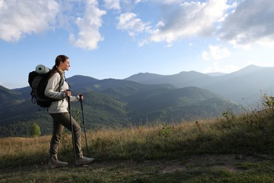 Tourist with backpack and trekking poles hiking through mountains, space for text
