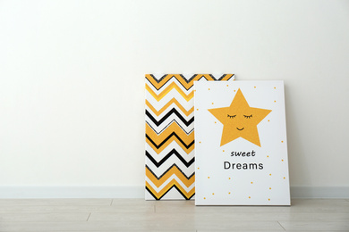 Adorable pictures of zigzag pattern and star with words SWEET DREAMS on floor near white wall, space for text. Children's room interior elements