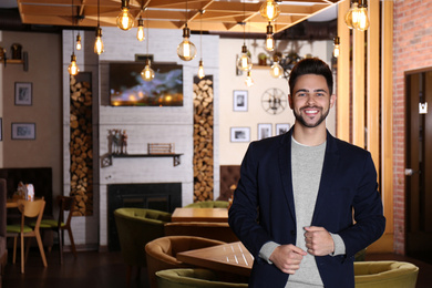 Young business owner standing in his cafe. Space for text