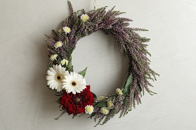 Beautiful autumnal wreath with heather flowers hanging on light grey background. Space for text