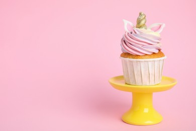Dessert stand with cute sweet unicorn cupcake on pink background. Space for text