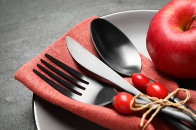 Festive table setting with rosehip berries and apple on black background, closeup. Thanksgiving Day celebration