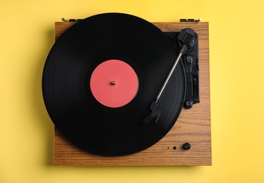 Modern vinyl record player with disc on yellow background, top view