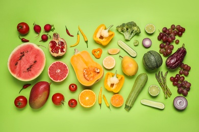 Fresh organic fruits and vegetables on green background, flat lay