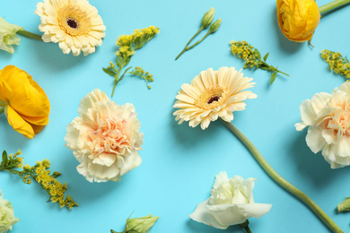 Floral composition with beautiful flowers on light blue background, flat lay