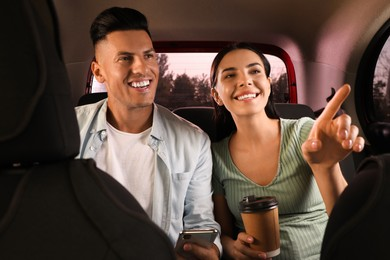 Happy couple with smartphone and cup of drink in modern taxi