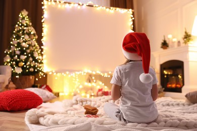 Little girl watching movie using video projector at home. Cozy Christmas atmosphere