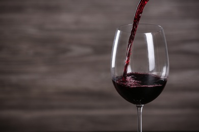 Pouring wine into glass on wooden background, space for text