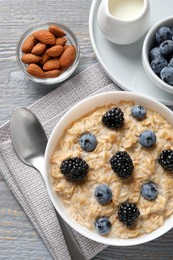 Tasty oatmeal porridge with blackberries and blueberries served on light grey wooden table, flat lay