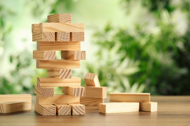 Jenga tower made of wooden blocks on table outdoors, space for text