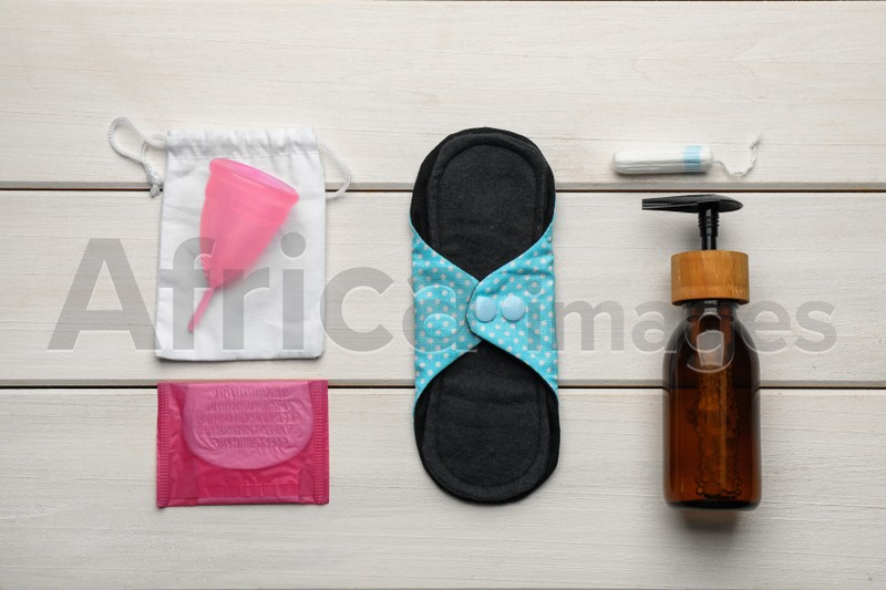 Cloth menstrual pad and other female hygiene products on white wooden table, flat lay