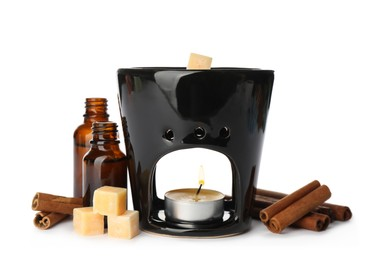 Stylish aroma lamp with essential wax cubes, oil and cinnamon on white background