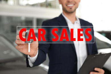 Salesman with key and clipboard in car dealership, closeup