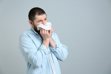 Man with tissue suffering from runny nose on light grey background. Space for text