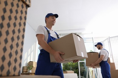 Moving service employees with cardboard boxes in room
