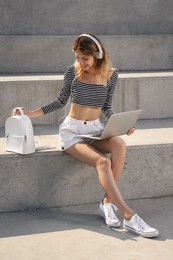 Young woman with stylish backpack and laptop on stairs outdoors