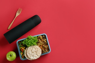 Thermos and lunch box with food on red background, flat lay. Space for text