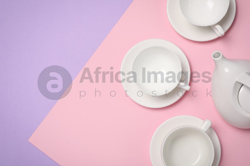 Cups with saucers and teapot on color background, flat lay. Space for text
