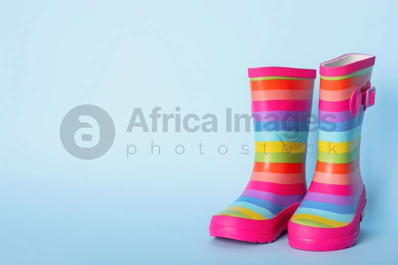 Pair of striped rubber boots on light blue background. Space for text