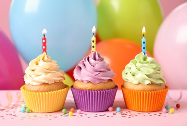 Birthday cupcakes with burning candles and sprinkles on pink table against color balloons, closeup