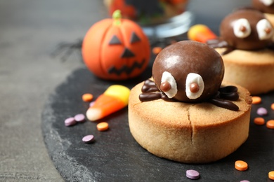 Delicious biscuits with chocolate spiders on grey table, closeup. Halloween celebration