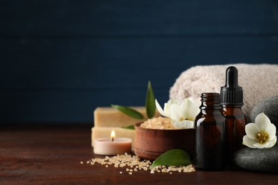 Composition with skin care products, spa stones and aroma oil on wooden table. Space for text
