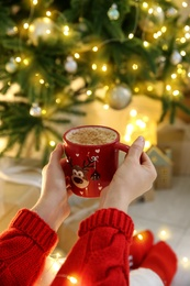 Woman holding festive cup with coffee near Christmas tree indoors, closeup