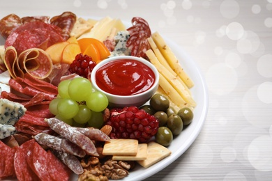 Plate of different appetizers with dip sauce on white wooden table, closeup. Bokeh effect