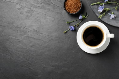 Cup of delicious chicory drink, granules and flowers on black table, flat lay. Space for text