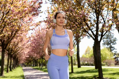 Woman with headphones on morning run in park. Fitness lifestyle