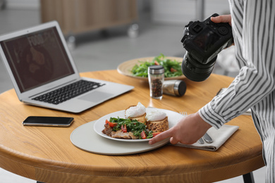 Food blogger taking photo of her lunch at wooden table, closeup