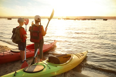 Children with paddles near kayaks on river shore, back view. Summer camp activity
