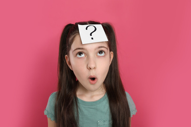 Emotional girl with question mark sticker on forehead against pink background